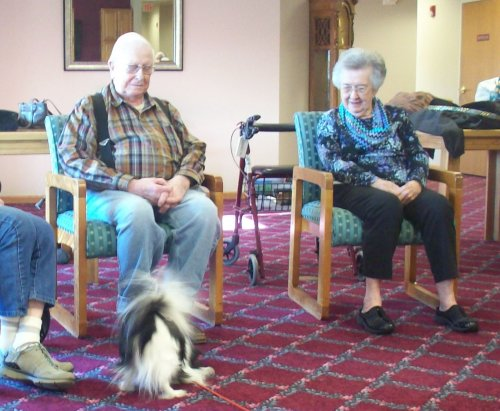 Residents Ralph and Vernice enjoy watching a therapy dog from Therapy Dogs International perform her tricks!