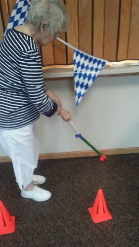 Norma P. does her best putting on the golf course for the Primrose Olympics.