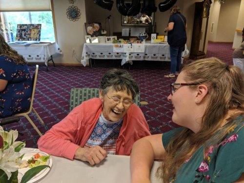 Lida R. exchanges laughs with LEC assistant, Mary D. 'What do you want to be when you grow up,' she asks at Mary's graduation party.