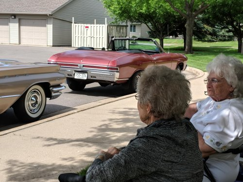 Loretta and Jane admire the cars under a shade tree. After all, the cars are not only hot, so is the temp!