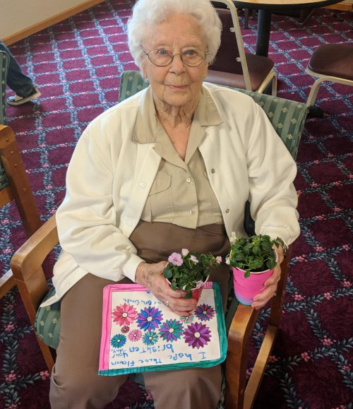 Arlyss receives a colored picture and plants from local elementary school students.
