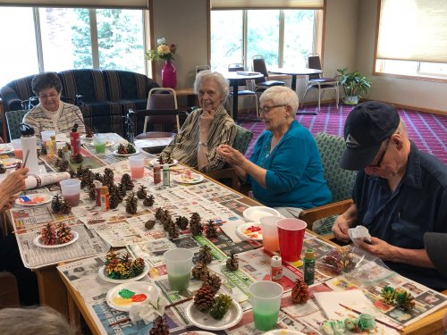 Residents enjoy painting pine cones as our fall craft. Now they each have something to be proud of displayed outside of their doors!