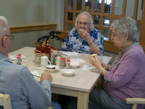 Residents Don, Gennie, and Norma enjoying a social hour while decorating cookies.
