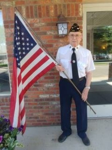 Resident Don O. proudly holding the American Flag after performing a Flag Ceremony at lunch for Memorial Day.