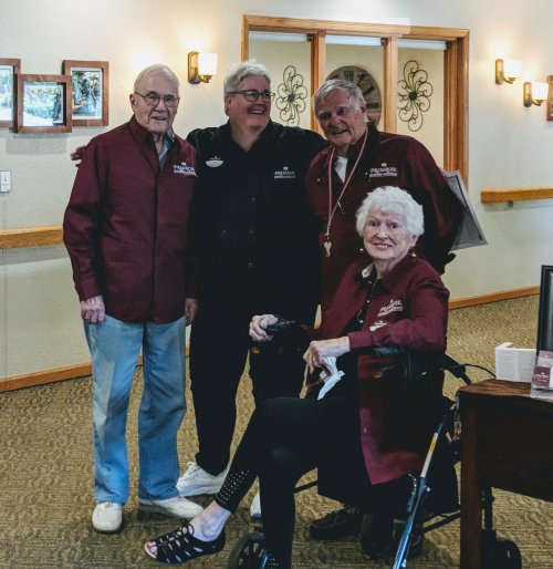 Lora, Primrose Director of Dining, shares a photo moment with Resident Ambassadors Don, Pat, and Ken.
