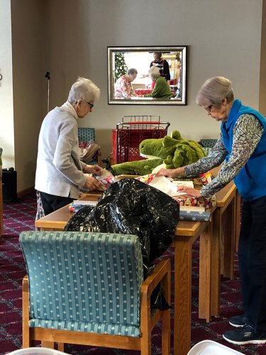 Jeanne and Marilyn hard at work wrapping gifts. Afterward, Marilyn said 'we had to get creative when it came to wrapping that alligator. It was so bulky but soft, it would have been much easier had we used a box!'