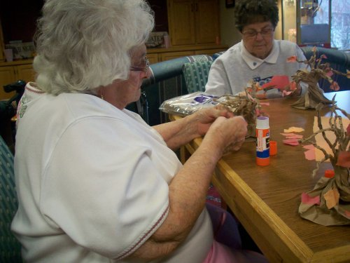 Jane and Monica meticulously placing their leaves on their fall craft!