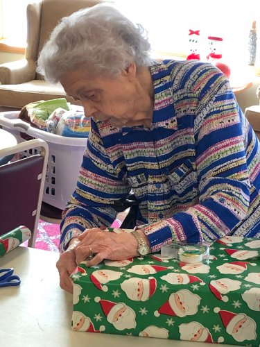 Resident Mary Ann helping wrap gifts for a local family in need. 'It's a lot of work wrapping all these gifts for families but to picture the smiles on their faces when the children open their gifts on Christmas day makes it all worth it!' she says.