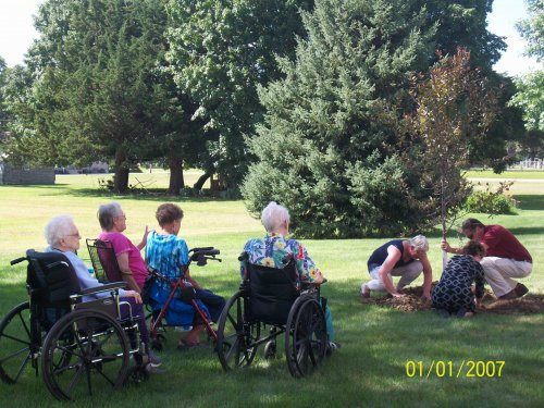 Residents watching the staff and Gordon's daughter plant a tree in his memoriam.