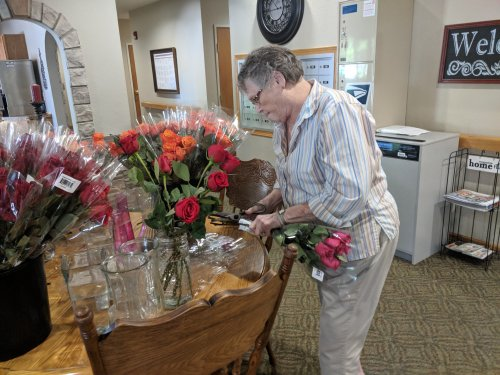 Joan arranges lovely roses donated by a local grocer.