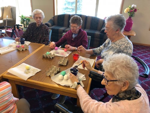 Residents gather to color Easter eggs. One resident said she enjoys coloring Easter eggs because it's tradition!