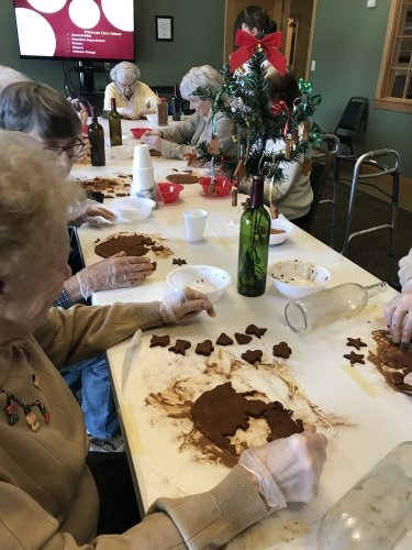 Residents having a fun time making wine bottle Charlie Brown Christmas trees