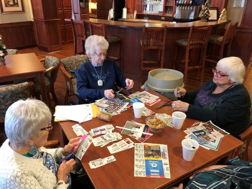 Our residents enjoy helping cut out coupons to send to the troops over seas.