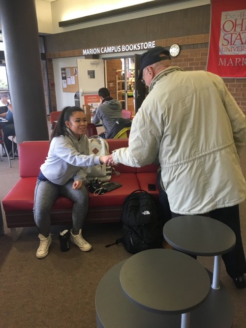Resident Loren Heiser hands out gift cards to students at The Ohio State University, Marion on Make a Difference Day, February 15, 2017.