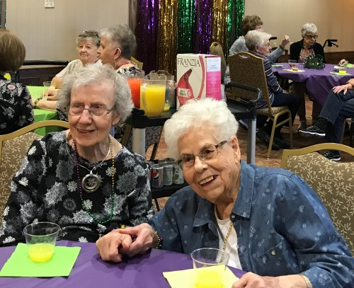 Friends catching up at the Mardi Gras Party