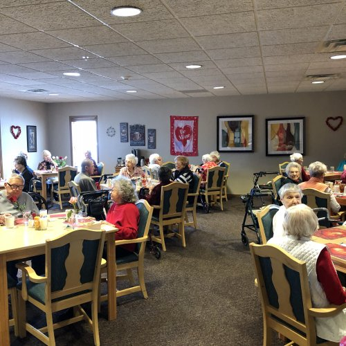 Residents enjoying thier Valentines lunch of prime rib complete with wine and roses.