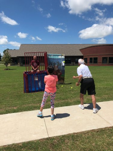 Len and Angie dunk the Primrose Maintenance Tech, Jim during the Resident/Staff Cookout! Food was provided by several local health organizations and residents could donate a dollar to the Frank and Barbara Broyles Foundation to throw a shot and dunk a staff member!