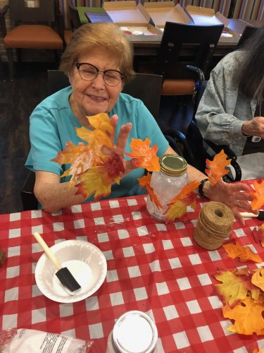 Residents spent a fun afternoon making Autumn Leaf Mason Jar Centerpieces for all of the dining room tables! Stella found out fast how sticky Mod Podge can be!