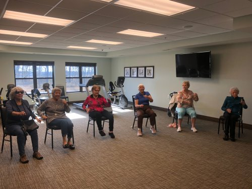 Primrose residents tapping their toes and moving their arms during a Chair Dance Fitness Exercise Class!