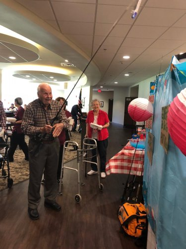 Ray playing 'Fish For A Prize' at the Fishing Themed Father's Day Luncheon full of musical entertainment by staff members, fishy snacks bar, and celebrating the men in our lives!