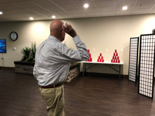 To celebrate National Fair Month in August, residents participated each Friday at lunch in a Midway Game where they played for prizes! Here, Sam is hoping to knock all of the cups down to win his sweetheart a teddy bear!