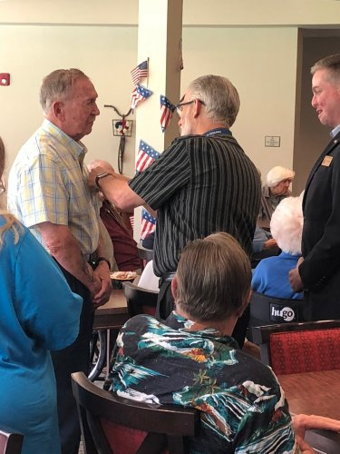 Paul receiving his Veteran Pin during the Primrose Veteran Pinning Ceremony facilitated by Arkansas Hospice's Doc Kenser and Corporal Aaron Mankin. Residents were awarded their pin and then saluted by the two veterans.