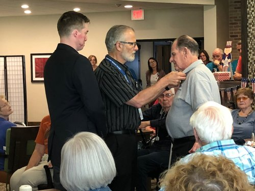 Walter receiving his Veteran Pin during the Primrose Veteran Pinning Ceremony facilitated by Arkansas Hospice's Doc Kenser and Corporal Aaron Mankin. Residents were awarded their pin and then saluted by the two veterans.