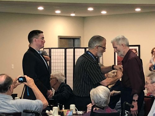 Bill receiving his Veteran Pin during the Primrose Veteran Pinning Ceremony facilitated by Arkansas Hospice's Doc Kenser and Corporal Aaron Mankin. Residents were awarded their pin and then saluted by the two veterans.
