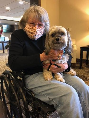 Judy poses with our maintenance technician's dog, Kimber during Pet Therapy!