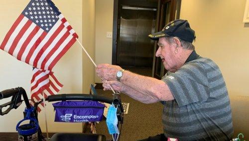 Spirit Day #3 Patriotic Car Parade. Residents began getting ready to watch their families and friends in the car parade by choosing signs and flags to hold! Walter decided to put flags on his walker and had his camera ready to capture each car!