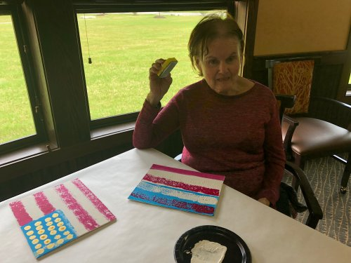 Our Memory Care LEC, Melissa led a very fun sponge painting class where residents created American Flag paintings for Memorial Day! Ann pauses to make sure painting is just right before adding the gold stars!