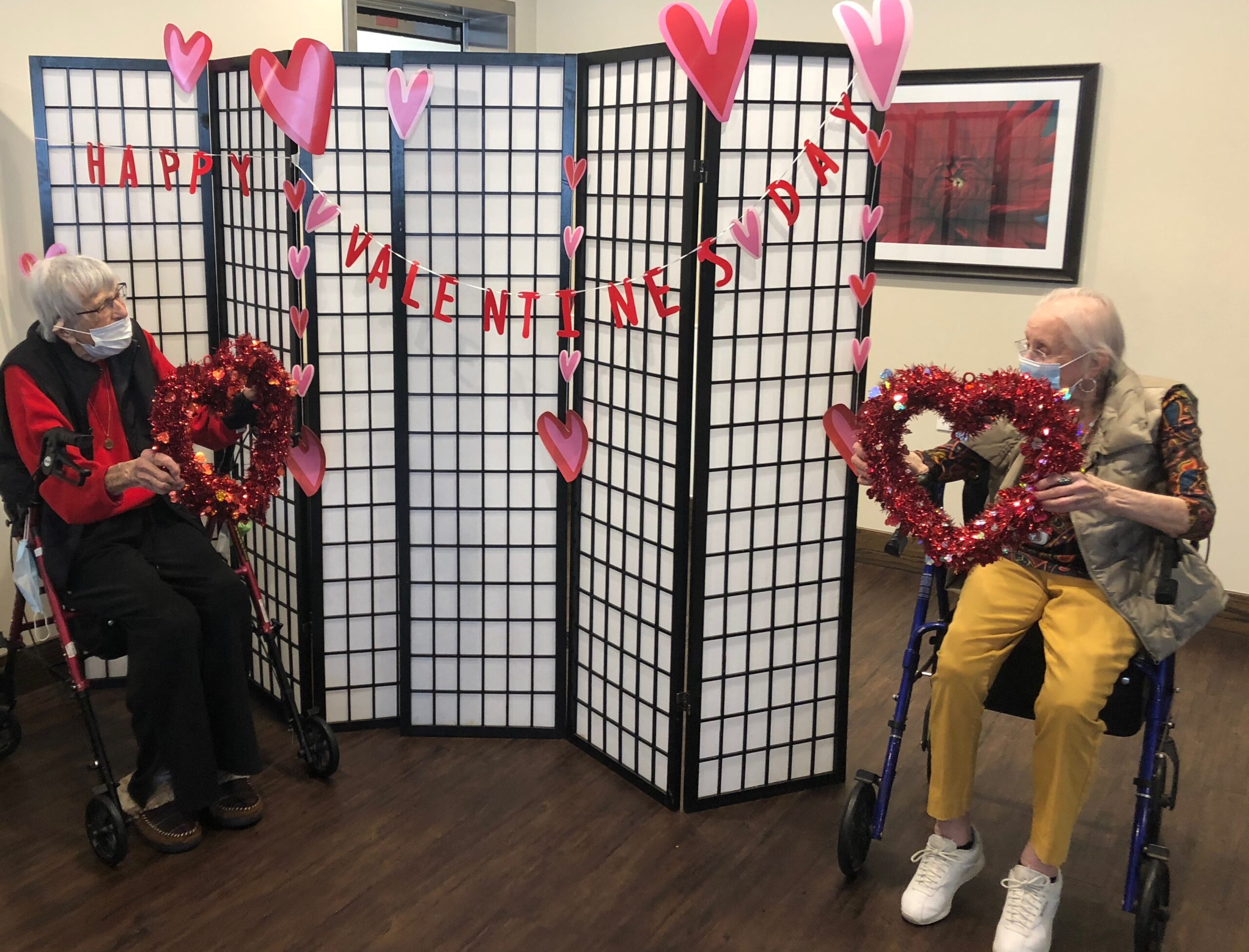 Valentines Day VIP Lunch-  New Friends, Anne and Sylvia pose in front of the Valentines Day backdrop as they enter into their VIP Valentines Luncheon! As residents made their way to the Primrose Dining Room they were given Valentines, Flowers, Strawberry Floats and more from the Primrose Staff! We celebrated our very important residents with a romantic lunch of Prime Rib, Chocolate Covered Strawberries and Bacon, and sweet love songs!