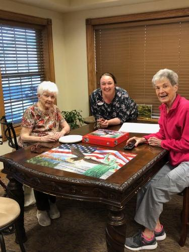 Tina (Executive Director) along with residents Marie and Cathy celebrating finishing a puzzle!
