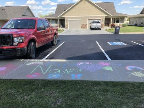 A resident's family leaving a message in sidewalk chalk