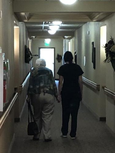 A member of our nursing staff walking with a resident down the hall.