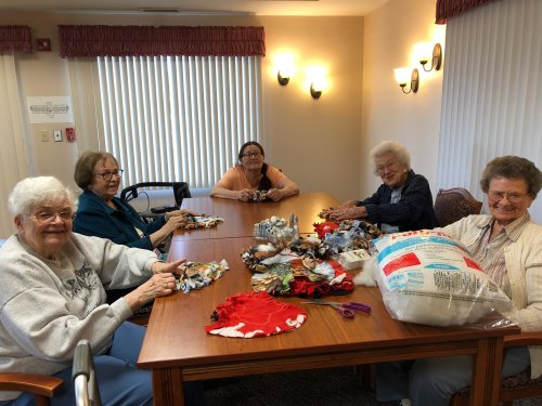 Residents working on dog toys for the Humane Society.