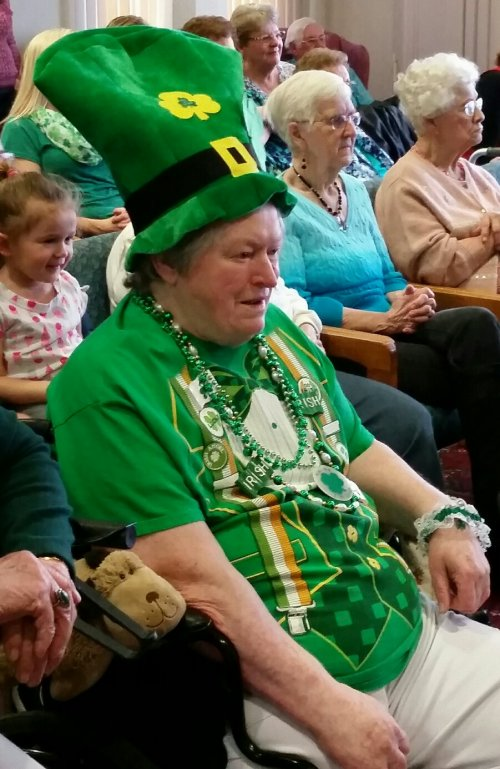 Resident is ready for our St. Patty's celebration she is watching the Irish dancers.