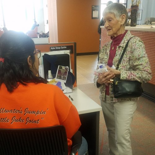 Darlene talking to a student for Random Acts of Kindness Day at the Oklahoma State Student Union.