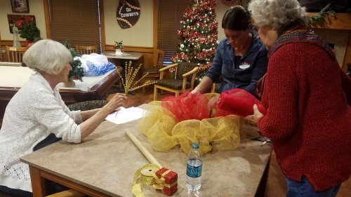 Charlotte and JoAn working together on a Christmas wreath.