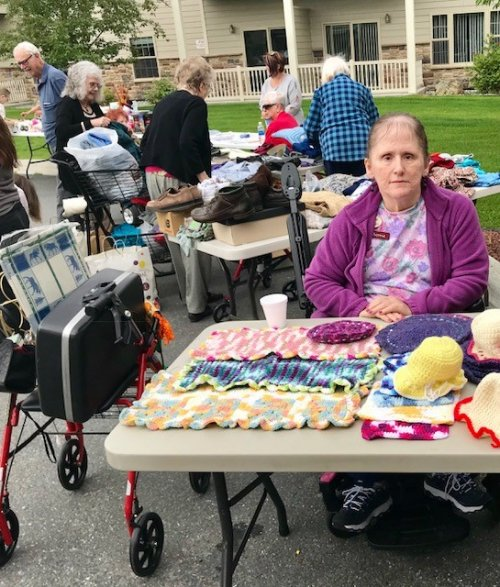 Resident Theresa selling her hand made items at the community rummage sale.