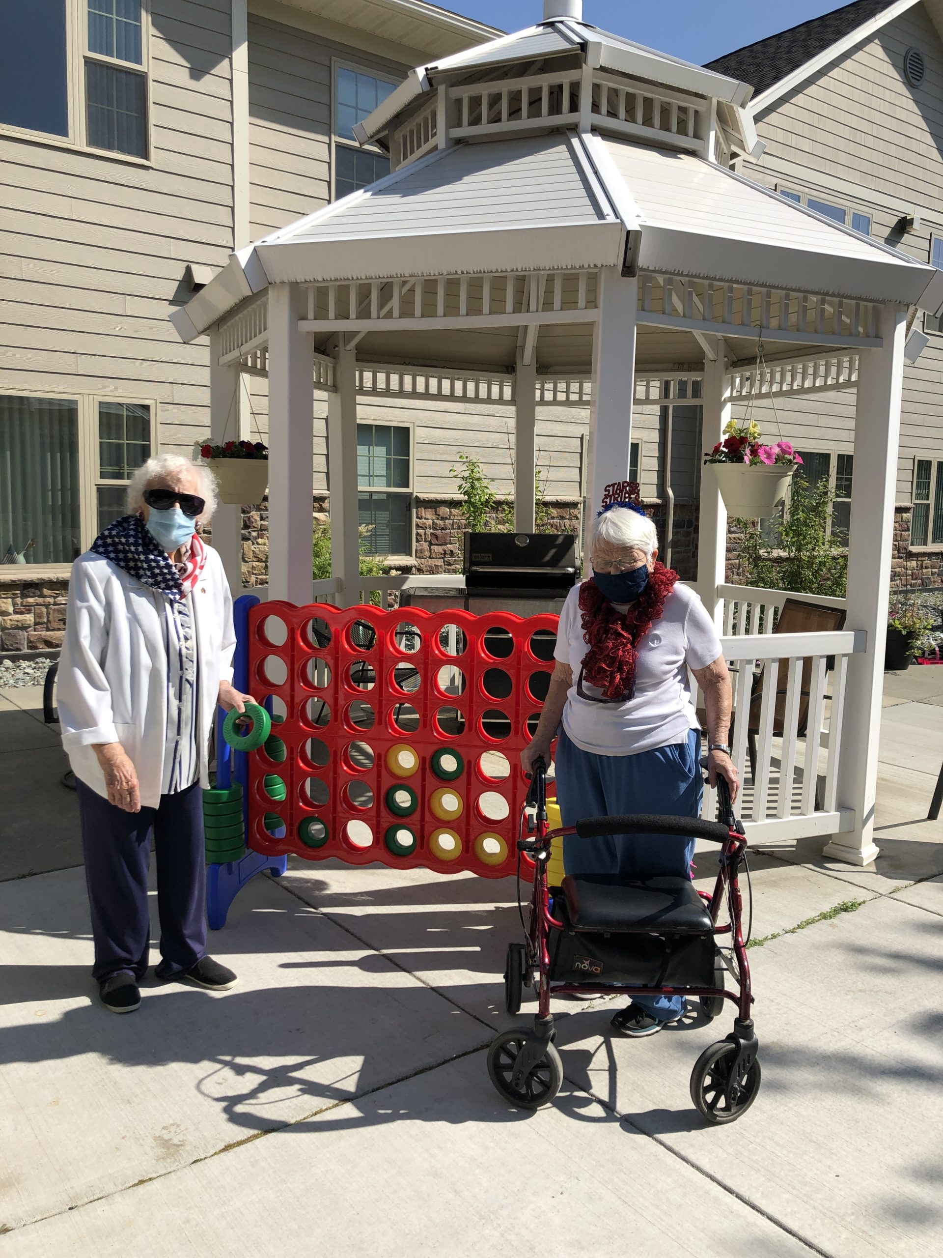 Phyllis & Jean enjoy a game of Connect Four outside.