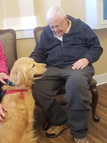 Paul visits with a pet therapy dog and truly enjoys the visit.