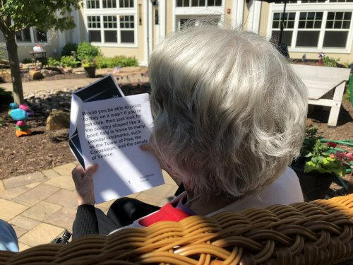 Judy reads 'place in Italy' out in the Courtyard on a beautiful day.