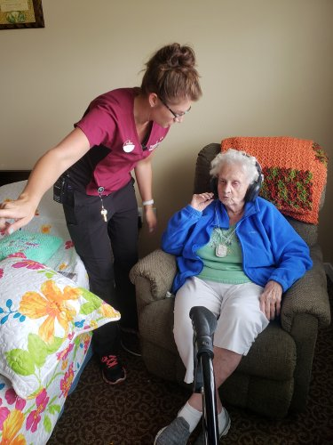 The nurse, Jennifer, assists Sally with her new headphones.