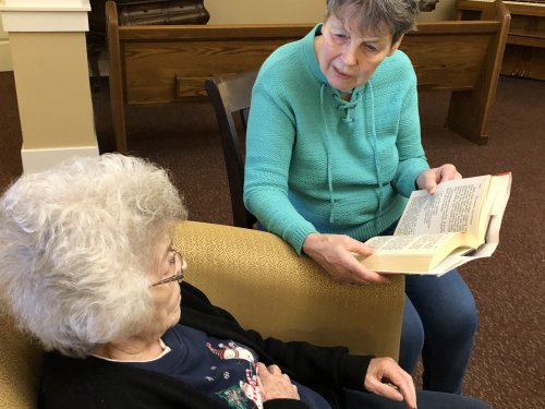 Residents are encouraged to help each other. Kathy reads stories to Mary Alice which they both enjoy reading.