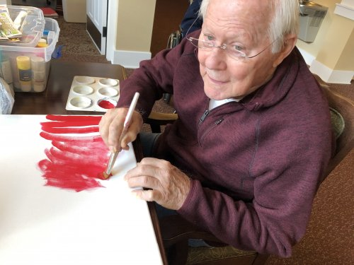 Bob paints a canvas to create his own art.