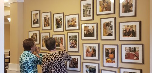 Shirley and Kathy look through all the pictures of the residents up on the wall. They enjoy reminiscing about the events and activities that go on.