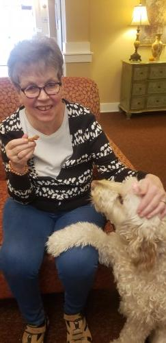 Kathy gives Marley a Homemade dog treat that the residents made during the week.