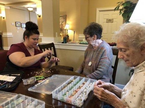 Andrea, our newest employee, helps make homemade necklaces with the residents using glass beads.
