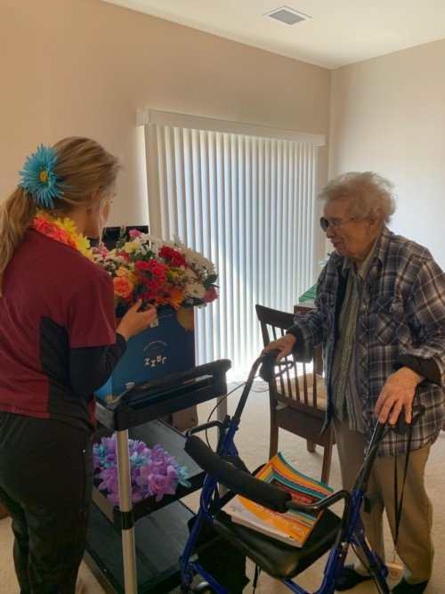 Bailey(CMA) Passing out flowers to resident Marilyn from a wonderfully generous community member that donated flowers to Primrose